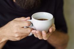 black coffee in hands on a dark background