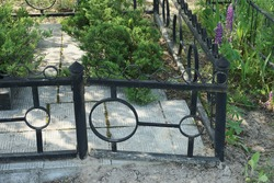 black  metal decorative fence made of iron bars at the grave in the cemetery