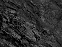 Black mountain texture. Close-up. Dark gray grunge background. Stone background. Black and white background. Monochrome rock texture.