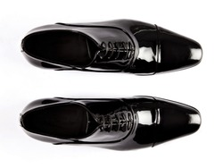 Black patent leather men shoes against white background