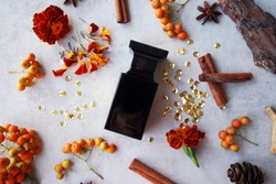 black perfume bottle with cinnamon sticks, orange flowers and bark fragments on gray background