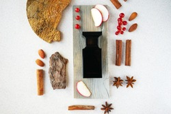 black perfume bottle with fragments of wood bark, cinnamon sticks, anise stars, slices of red apples and currants. Concept of autumn woody fruity scent
