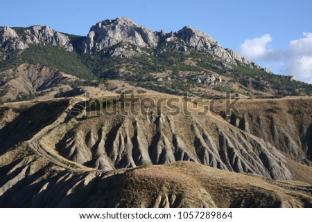 Black sea. Panoramic view of the Kara Dag Mountain and Kurortnoe settlement on the coast of Black Sea in Crimea. Picturesque small beach lit by the sun. Crimea. Ridge Kara Dag. Settlement Kurortnoe.