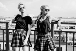 Black white portrait portrait of two pretty hipster blonde sisters  wearing plaid skirt and  black T-shirt. Girls smile, have fun against  urban city.