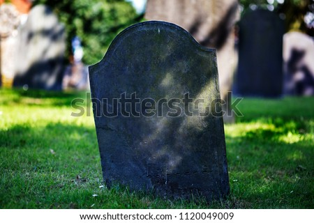 Blank gravestone in graveyard. Old, decayed and grunge, ready for text. Trees and graves in background.