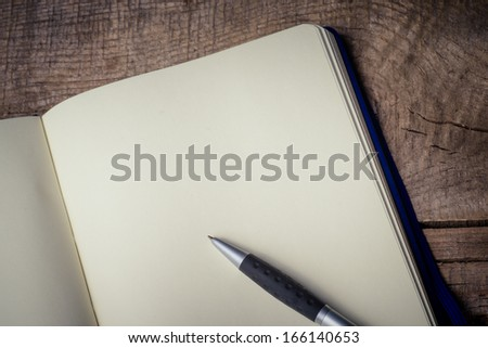 Blank notepad with pen on office wooden table