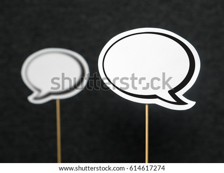 2 blank speech bubbles on a dark black background. The other speech balloon blurred. Chat bubble cut from paper with wooden stick. Discussion, protest and commenting concept with copy space for text. #614617274