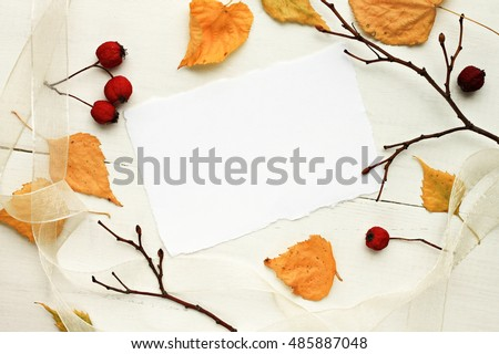Blank white paper note framed dried yellow autumnal leaves, bare branches, red berries. Fall background.