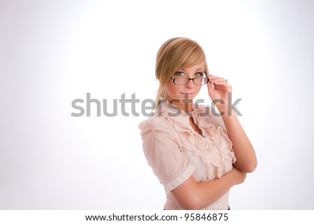 blonde businesswoman on white background in business attire adjusting her glasses