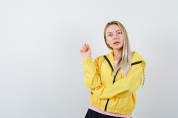 blonde girl in pink t-shirt and yellow jacket raising one hand in eureka gesture while holding hand on elbow and looking alluring , front view.