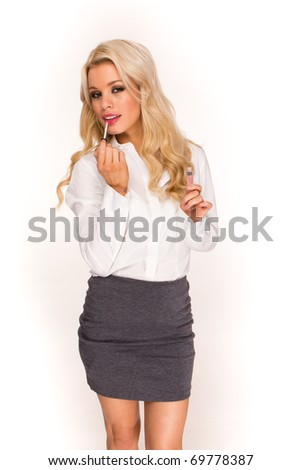 blonde sexy business lady applying cosmetics at workplace