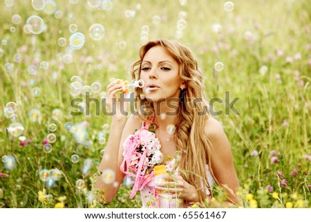 Blonde starts soap bubbles in a green field