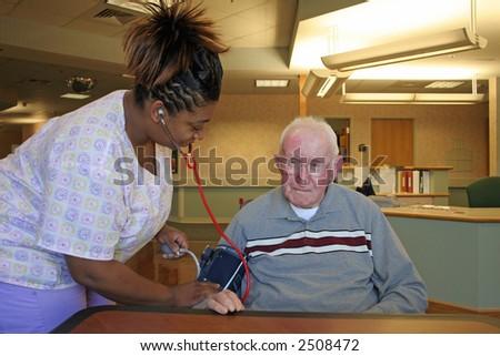"""Blood Pressure Check"" Nursing staff checking blood pressure of nursing home resident."