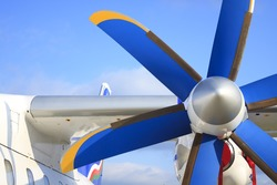 Blue and yellow wing with propeller of the passenger plane