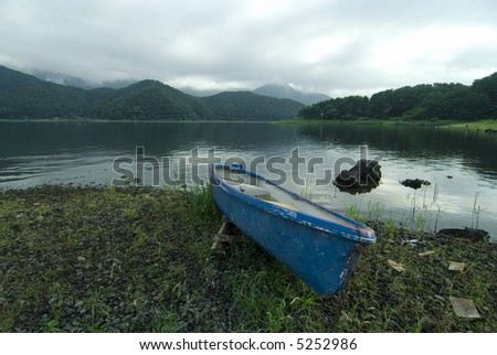 blue boat on the scenic mountain lake's shore at wet summer cloudy  weather