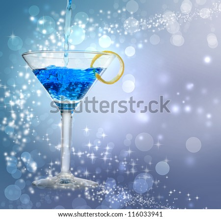 Blue cocktail being poured into a glass on abstract lights background
