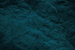Blue green grunge background. Toned rock texture background. Dark stone background. Combination of teal color and rough cracked rock surface.