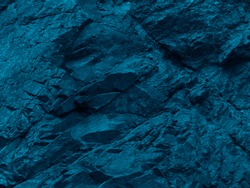 Blue green rock background. Toned mountain texture. Close-up. The combination of dark turquoise color and volumetric stone texture. 3D effect.