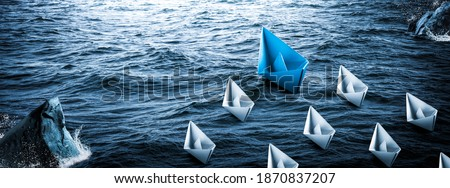 Blue Paper Boat Leading A Fleet Of Small White Boats Around Rocks In Rough Water - Leadership Concept