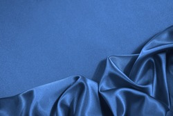 Blue silk satin fabric background. Copy space for your design. Delicate wavy folds. Beautiful elegant blue background.