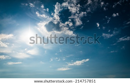 Blue sky with sun and clouds. With lens flare effect.