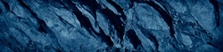 Blue stone background. Toned monochrome rock texture. Close-up. Blue grunge banner with copy space for your design.