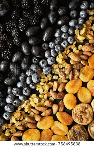 blueberry, dried apricots, grapes, blackberry, plum, raisins, almond and dried figs on dark background #756495838