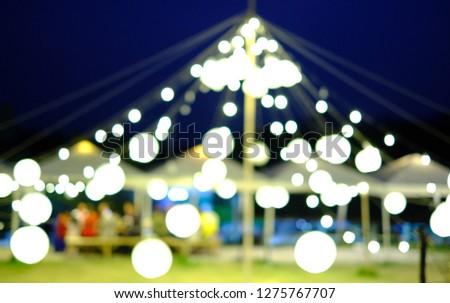 ฺBlur picture of circular lamps hanging above a triangle tent around a camp. Bokeh concept.