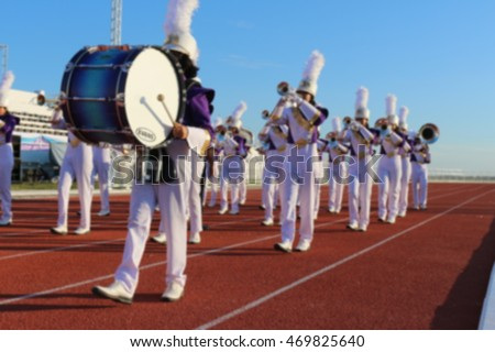 Blur purple white uniform marching band in sport day parade on \nstadium in Chaiyaphum Rajabhat University Thailand