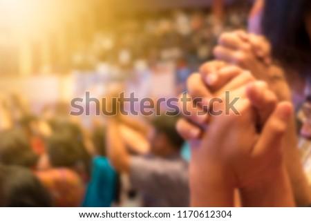 ฺBlurred of Christian congregation holding hands and worship God together in big Concert hall with music stage light effected. christian background with copy space.