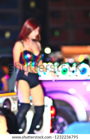 blurred photo Coyote, Asian Girl Dancing On the car with audio And there are lights on various colors decorated on the car. At the Motor Show in Thailand
