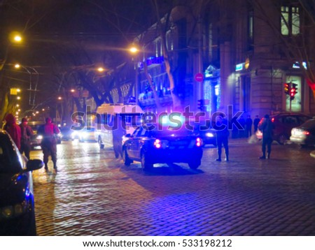 Blurred police car on the street at night. Orange cones set up to direct traffic around a police car in the collision scene. Great background blur