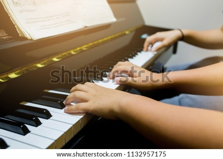Blurry picture of woman teaching boy to play the piano with selective focus. Four hands from two people playing piano. with selective focus. #1132957175