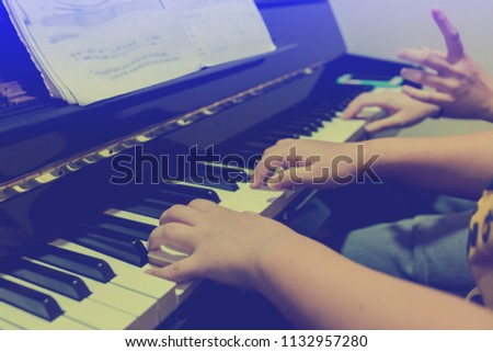 Blurry picture of woman teaching boy to play the piano with selective focus. Four hands from two people playing piano. with selective focus. #1132957280