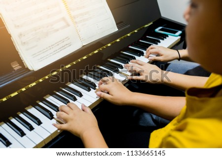 Blurry picture of woman teaching boy to play the piano with selective focus. Four hands from two people playing piano. with selective focus. #1133665145