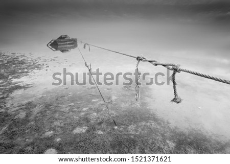 Boat stranded on the beach with rope tightened in black and white long exposure shot. image contains grains and soft focus due to long exposure technique