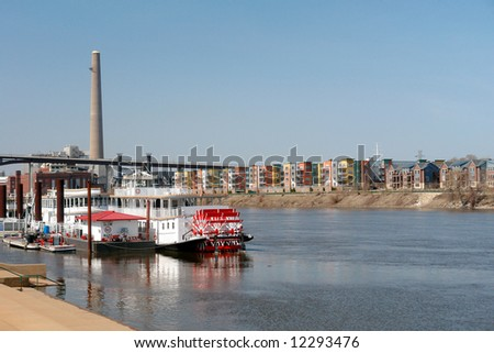 Boats on the Mississippi River with residential houses in the background