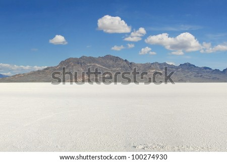 Bonneville Salt Flats in early morning. Mountains in center and a bright blue sky above with several puffy white clouds./ Classic Bonneville Salt Flats View / Lots of beauty and and but very harsh.