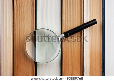 books and magnifying glass - stock photo