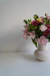 Bouquet with pink alstroemeria and lila  eustoma/lisianthus  in a white ceramic vase on the grey background