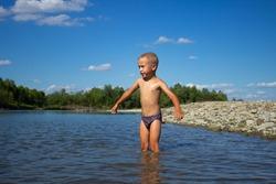 boy bathes in a mountain river