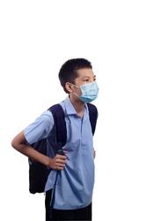 ฺBoy in school uniform, carrying a backpack, school supplies, wearing a disposable medical mask, standing two meters apart, the concept is Socialdistancing. To prevent COVID-19 infection