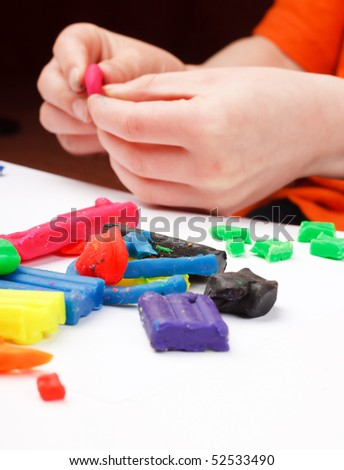Boy moulds from plasticine on table