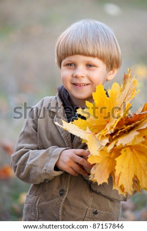 boy with red autumn leaves