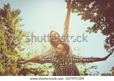 Boyfriend carries the girl on her piggyback with open arms. Couple in nature.