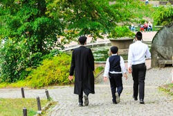3 boys , a family of Hasidic Jews, in traditional clothes walk in the park in Uman, Ukraine, the time of the Jewish New Year, Religious Orthodox Jew