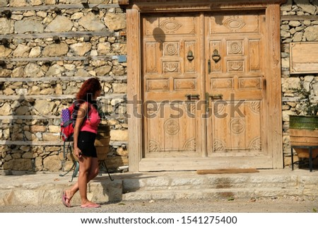 İbradı Antalya Turkey Düğmeli Houses ( Buttoned houses ) which have traditional architectural style of Anatolia. a girl tourist with backpacks visited this region with interest in  15 september 2019.