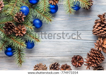 Branches of a Christmas tree with blue balls and cones on a wooden turquoise background. New year. Christmas.    #774973354