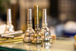 3 Brass mouthpieces arranged on a glass shelf at a music repair shop. A trumpet, trombone, and euphonium mouthpiece.