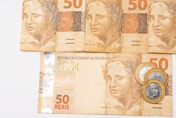 Brazilian money, 50 reais notes   and coins on banknotes, financial health. on a white background